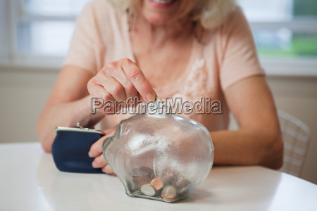 senior woman saving money in piggy