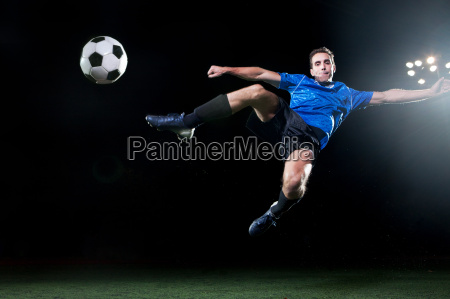 young soccer player leaping into air
