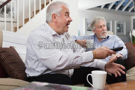senior men looking at television in