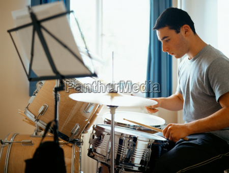 teenage boy playing the drums
