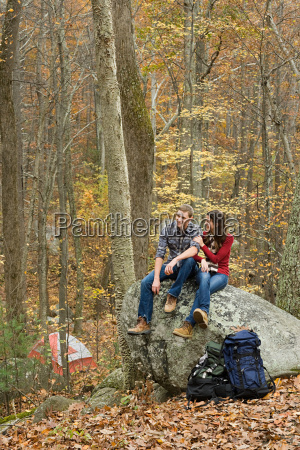 young couple sitting on boulder in