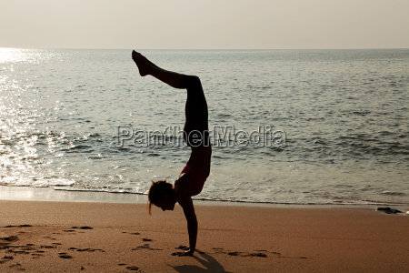 woman practicing yoga on a beach