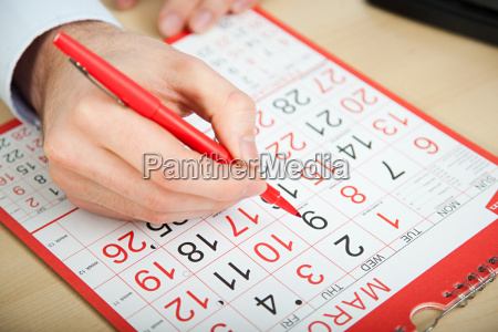 office worker marking calendar with red