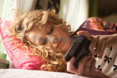 teenage girl lying on bed with