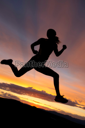 silhouette of athlete jumping against sunset