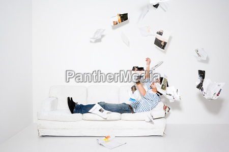 man throwing pages of a magazine