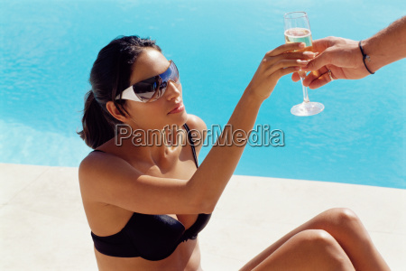 woman being passed a champagne glass