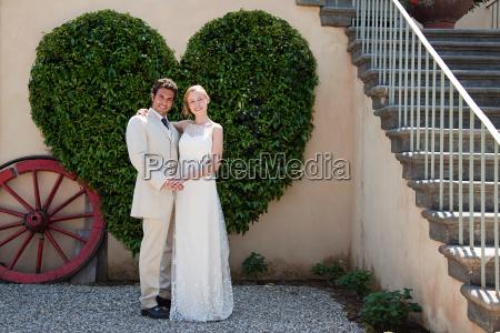 newlyweds by heart shaped bush
