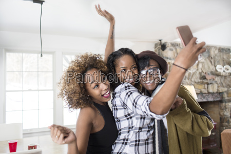 three young women posing for smartphone