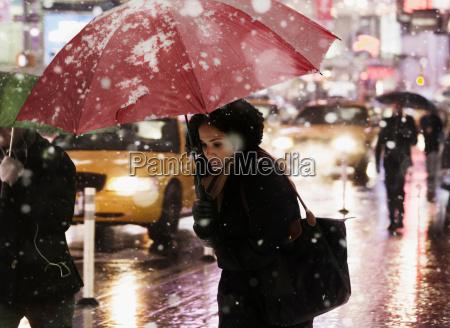 woman walking through city street in