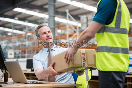 man delivering cardboard box to another