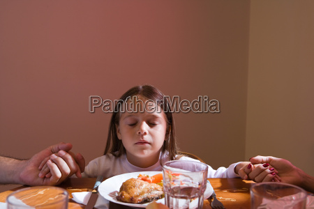 family holding hands at dinner table