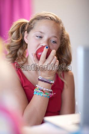 girl eating apple at desk