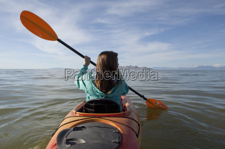 rear view of young woman kayaking