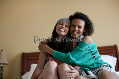 young women embracing on bed portrait