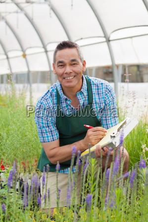 mature man holding clipboard in garden
