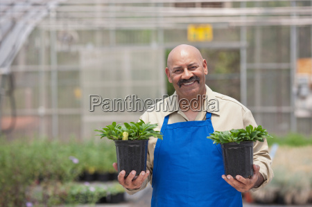 mature man holding plant pots in