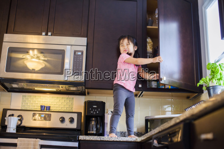 young girl standing on kitchen work