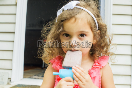 portrait of young girl eating ice