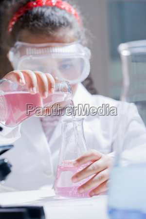 girl pouring chemicals into conical flask