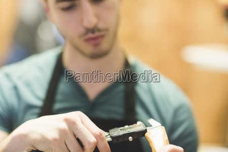 young man wearing apron crafting wood