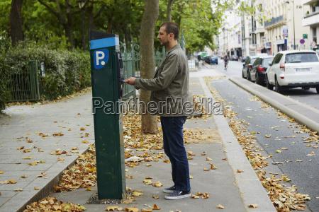 mid adult man using parking meter