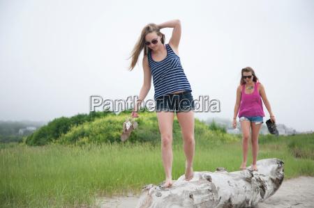 young women walking along log on
