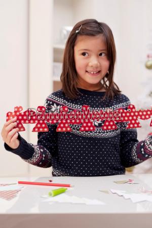 girl holding christmas decoration smiling