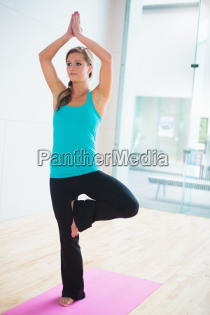young woman on yoga mat in