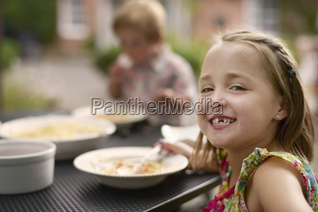 girl dining at garden table looking