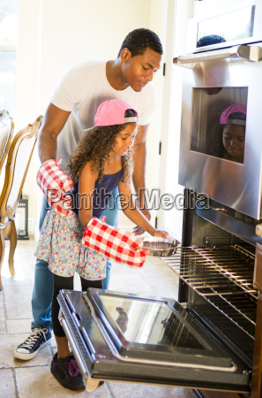 father helping daughter insert cake tin