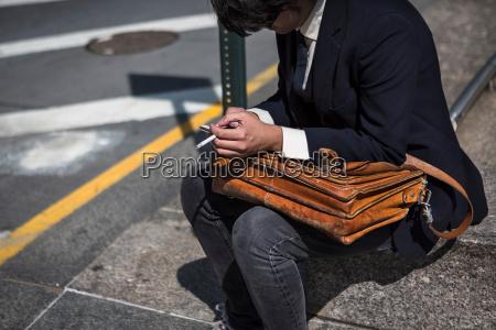 businessman sitting on kerb with satchel