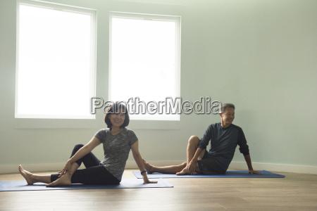 mature couple sitting on yoga mat