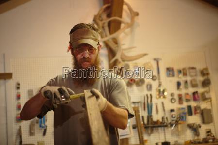 wood artist in workshop measuring wood