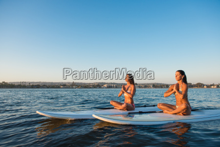 two women in lotus position on