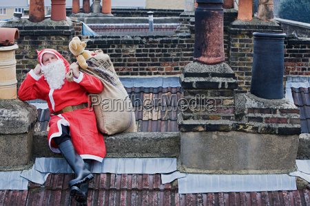 santa claus sitting on a roof