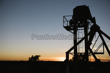 silhouetted agricultural structure at sunset