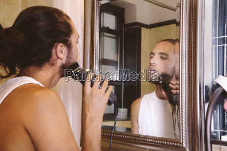 young man looking in mirror shaving
