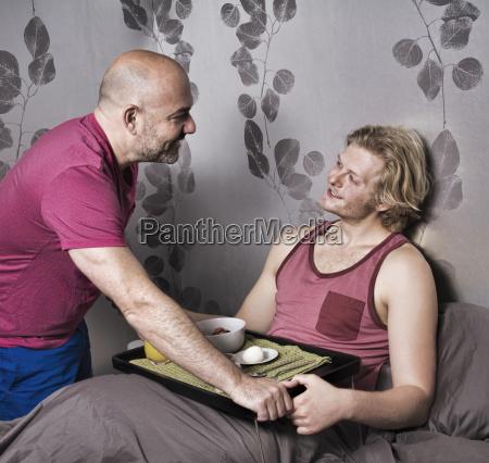 mature man handing breakfast in bed