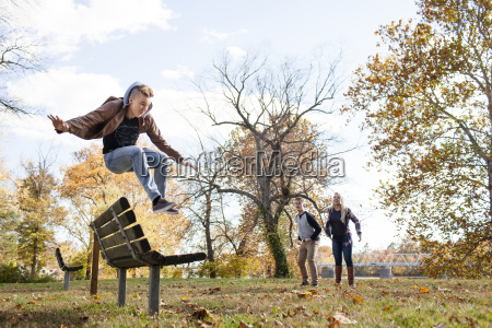 teenage boy jumping over park bench