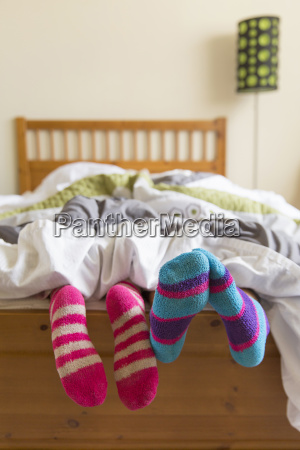 young women in bed underneath quilt