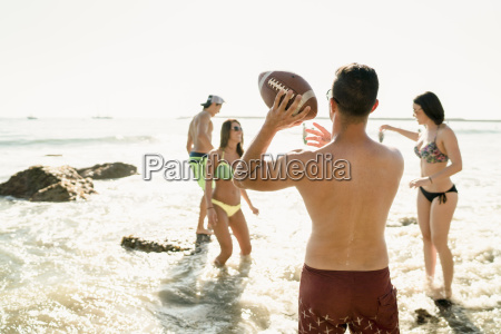 young adult friends playing american football