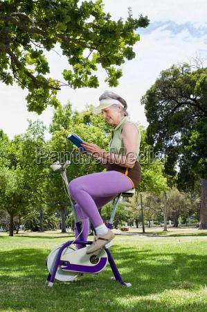 senior adult woman riding exercise bike