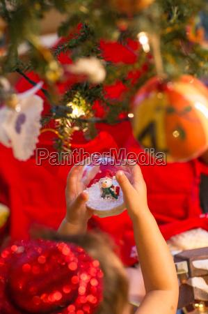 little girl holding snow globe ornament