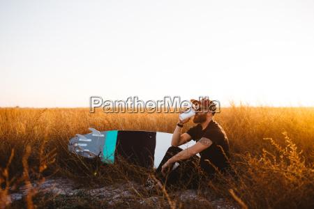 male surfer drinking coffee in field