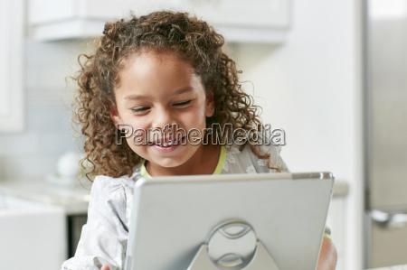 girl using digital tablet looking down