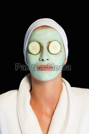 woman wearing facial mask and cucumber