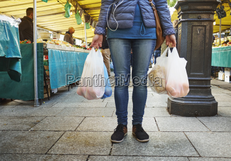 young woman at market holding bags