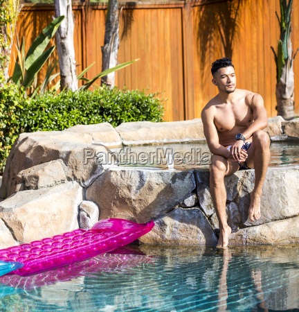 young man sitting on garden swimming