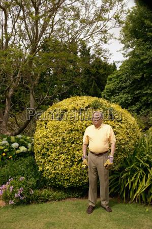 senior man stood in a garden